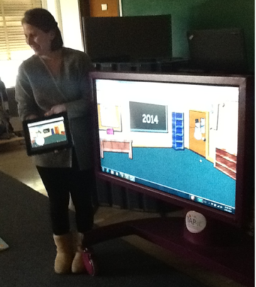 Teacher using iPad and TAPit to facilitate a lesson for multi-handicapped students