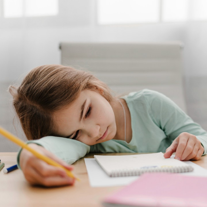 Child with pencil and notebook laying their head on right arm looking bored