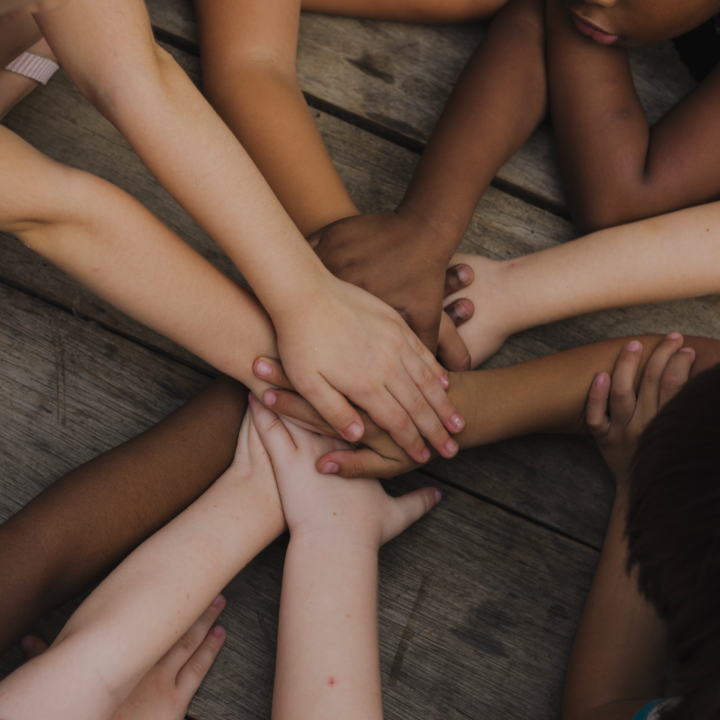 Children with diverse skin tones laying in a circle stacking hands