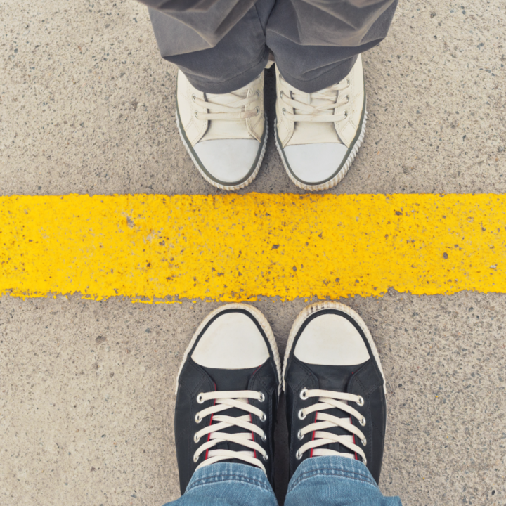 Sneakers from above. Two people standing toe to toe at dividing line