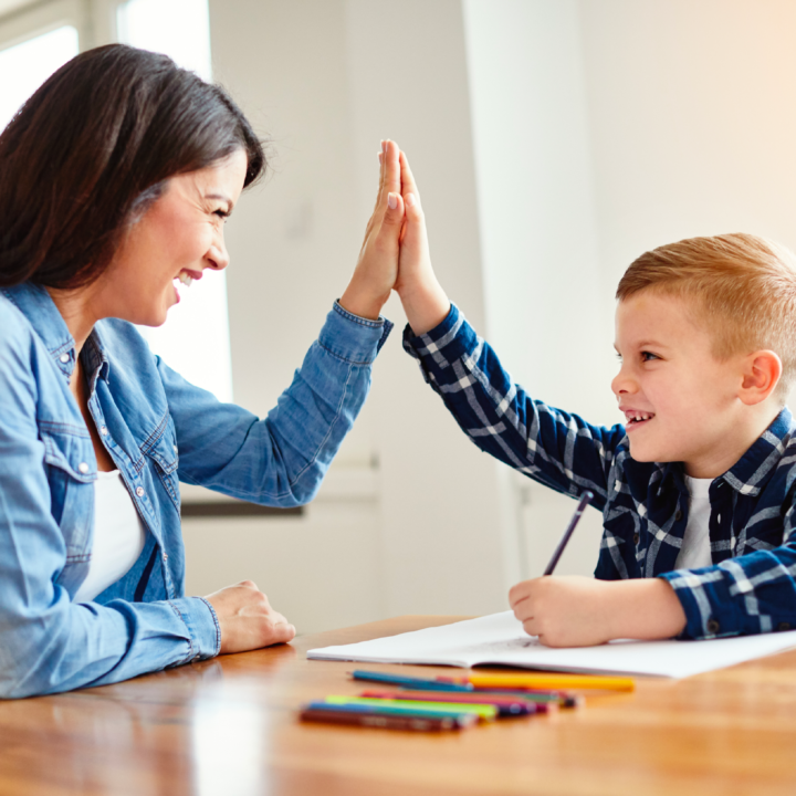 Woman and child smiling and high-fiving each other as the child writes in a workbook with colored pencils