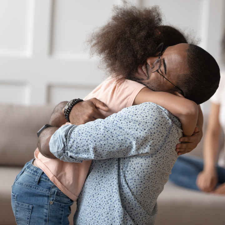 Man with glasses smiling while embracing his daughter