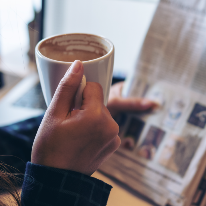 Person relaxing and reading newspaper with cup of coffee in hand