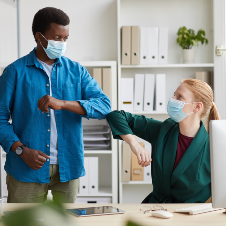 Building employee morale - Seated woman wearing mask bumps elbows to greet man standing next to her, also wearing mask
