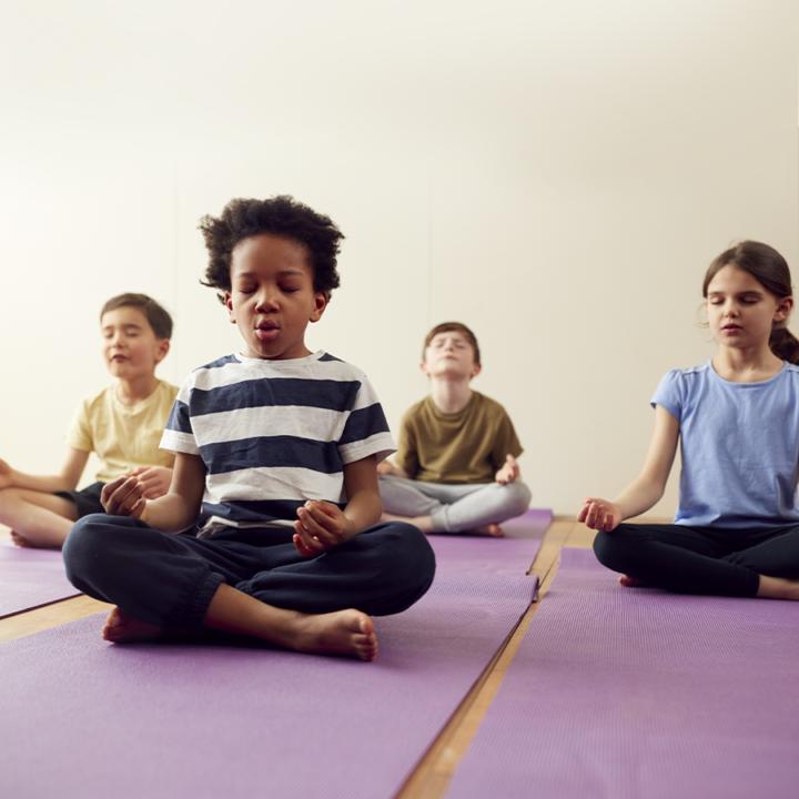After school programs - four children sitting on yoga mats meditating