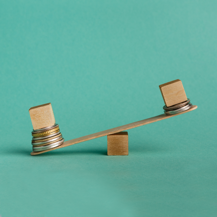 Personal biases - Blue background. Two wooden cubes sitting on piles of coins on opposite ends of a teeter totter. The left cube is the one on the ground because it has more coins underneath.