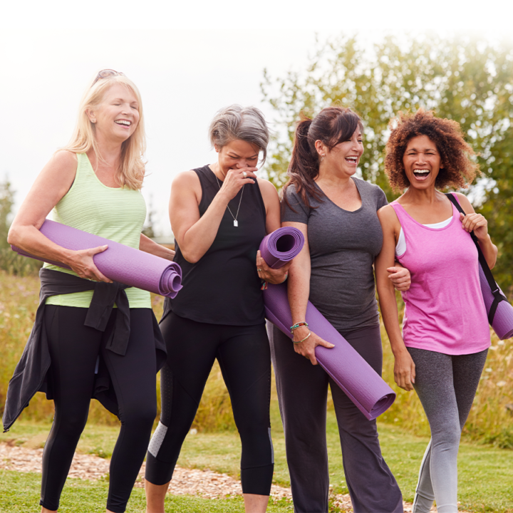 Does exercise make you happy? Four women walking together outside, holding yoga mats and laughing.
