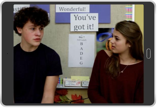 boy talking to girl by bulletin board